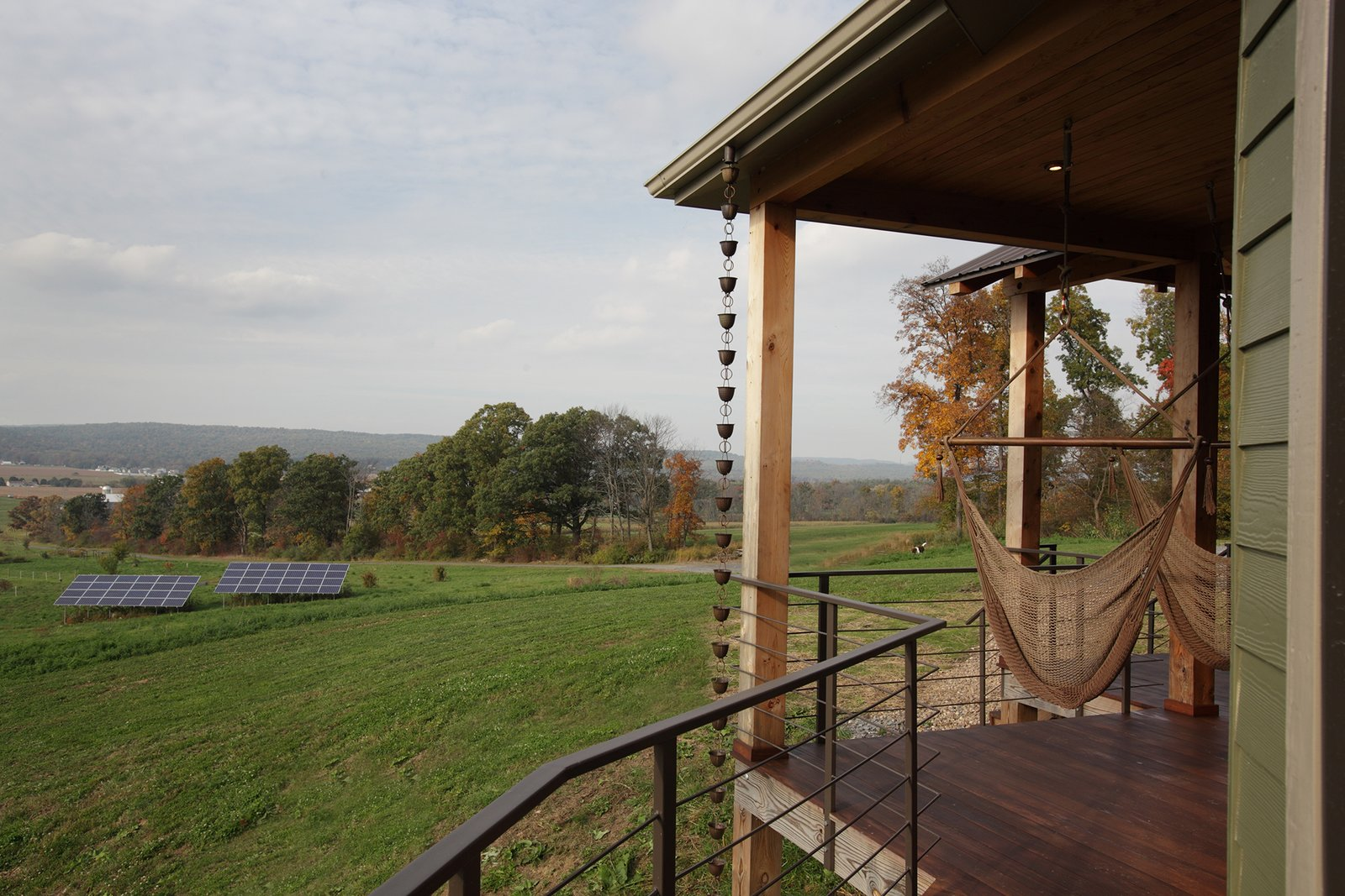 Located outside of State College, Pennsylvania, the home enjoys rolling green vistas. Two hammocks on the porch are ideal places to take in the views or a good book. The solar array, pictured in the midground, powers the home.  Photo 5 of 7 in A Round Pennsylvania Prefab Offers 360-Degree Solutions in Sustainability