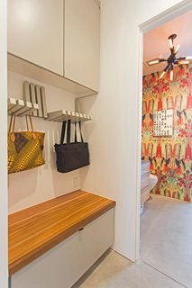 A clever storage area holds purses and bags, while a bench hides away bulkier items.