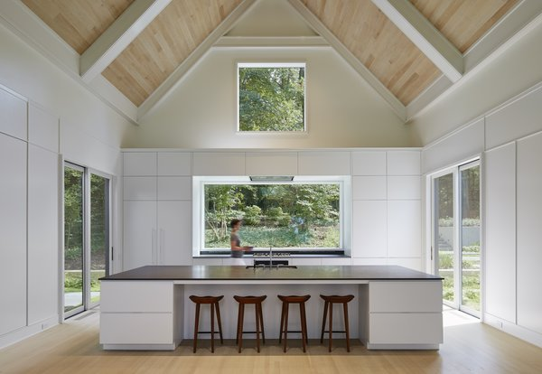 """Two smaller sliding doors lead outward from the kitchen, which continues the home's minimalist aesthetic. Booth Hansen chose to paint the window interiors white to match the neutral color palette. """"When you're looking out the windows, the house takes a backseat to the environment,"""" says Sandschafer."""