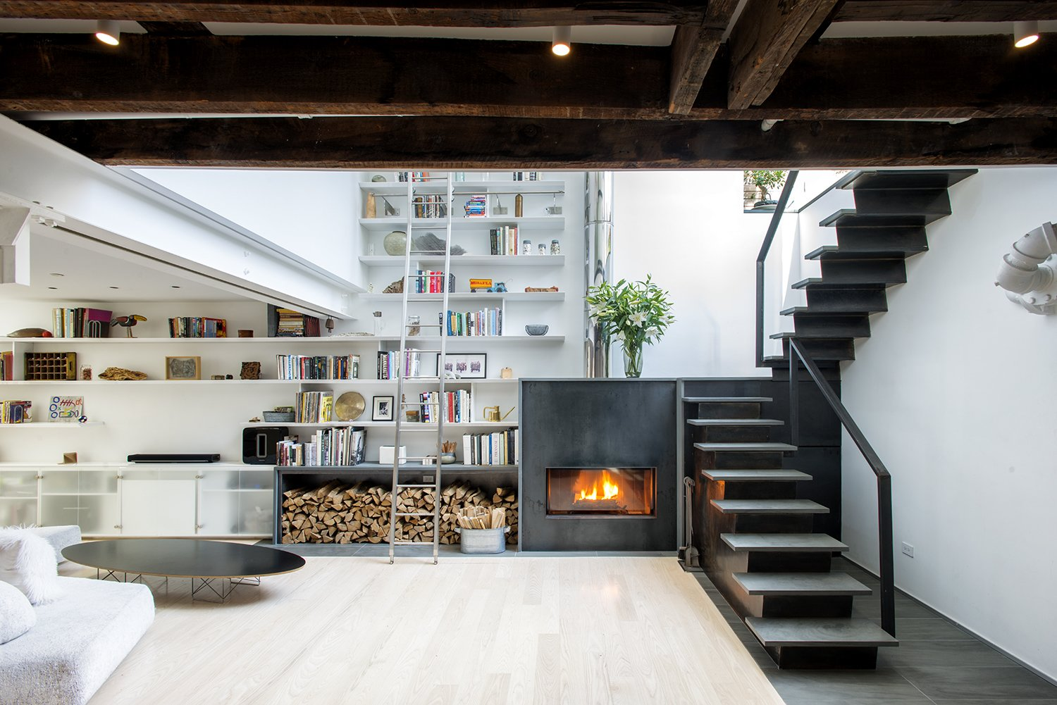 Living Room, Storage, Ceiling Lighting, Coffee Tables, Shelves, Wood Burning Fireplace, Light Hardwood Floor, Sofa, and Bookcase  Photo 1 of 10 in A Rooftop Addition on a 19th-Century Building Suits a Growing Family's Needs