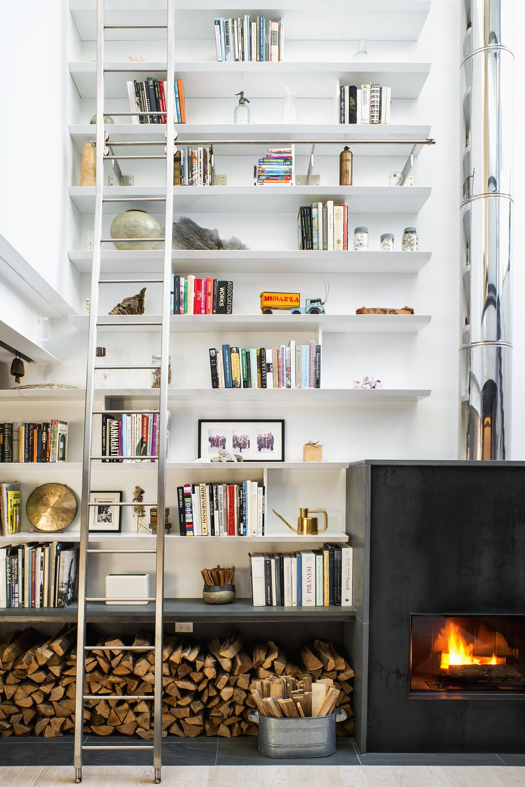 The double-height living room provided the perfect opportunity to combine the homeowners' love of art, literature, and travel, allowing them to fill the 24-foot shelves with books and collected artifacts. A wood-burning sustainable fireplace by Wittus adds a broad stroke of warmth. Tagged: Living Room, Standard Layout Fireplace, Wood Burning Fireplace, Bookcase, Shelves, and Light Hardwood Floor.  Photo 5 of 10 in A Rooftop Addition on a 19th-Century Building Suits a Growing Family's Needs