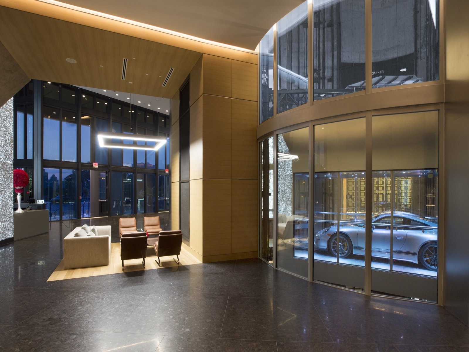 The project architect was Sieger Suarez, with interior design by Michael Wolk Design Associates and Porsche Design. Here, a glass car observatory allows a glimpse of cars as they float by on the Dezervator, named for the developer Gil Dezer.  Photo 3 of 11 in Porsche Design's Lavish Residential Tower in Miami Lifts Residents and Cars Sky High