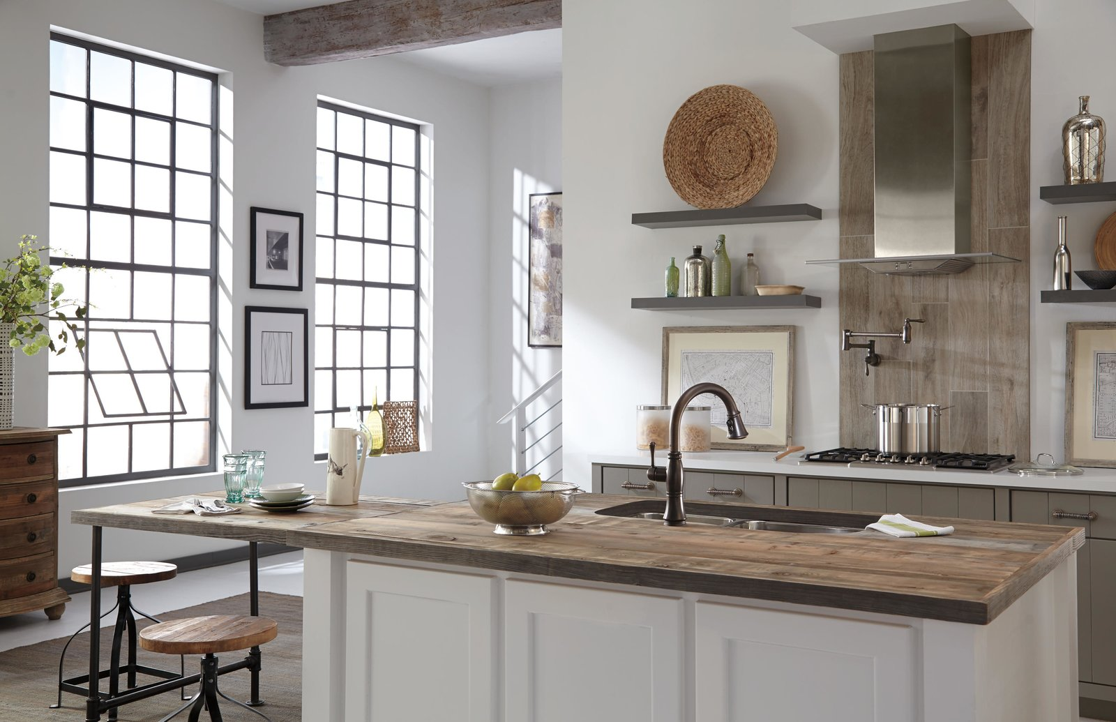Kitchen with raw wood island countertop white cabinets and warehouse style windows.