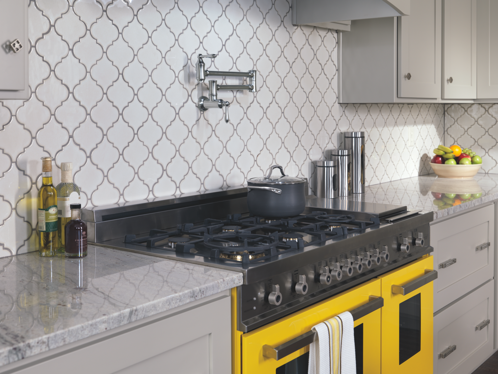 Kitchen with bright yellow range, grey cabinets and patterned tile backsplash.
