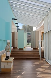 A glass atrium holds together four of the six pavilions that make up the home. Sottsass considered hallways to be unimaginative, preferring to create a flexible village of connected spaces. Above, an architectural light fixture grows organically from the blue wall.