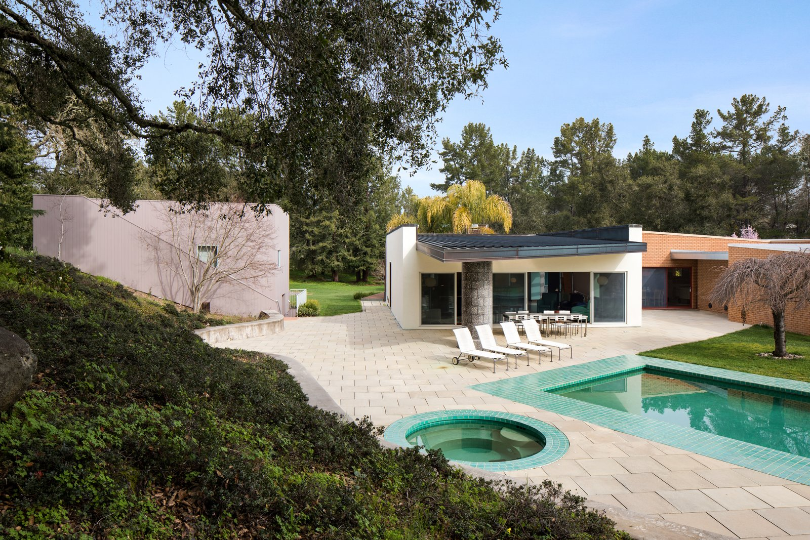 The pool and outdoor hot tub bounce green light off the roof hanging over the back terrace, creating a lush environment.  Photo 10 of 12 in IDEO Founder David Kelley Asks $13.5M For His Ettore Sottsass-Designed Masterpiece