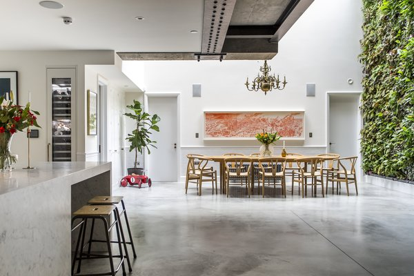 The living room, kitchen, and dining room sit below street level in an open, communal area. A large, operable skylight measuring six by three meters allows light to stream over the dining table—the four glass panes had to be craned over the neighboring buildings.