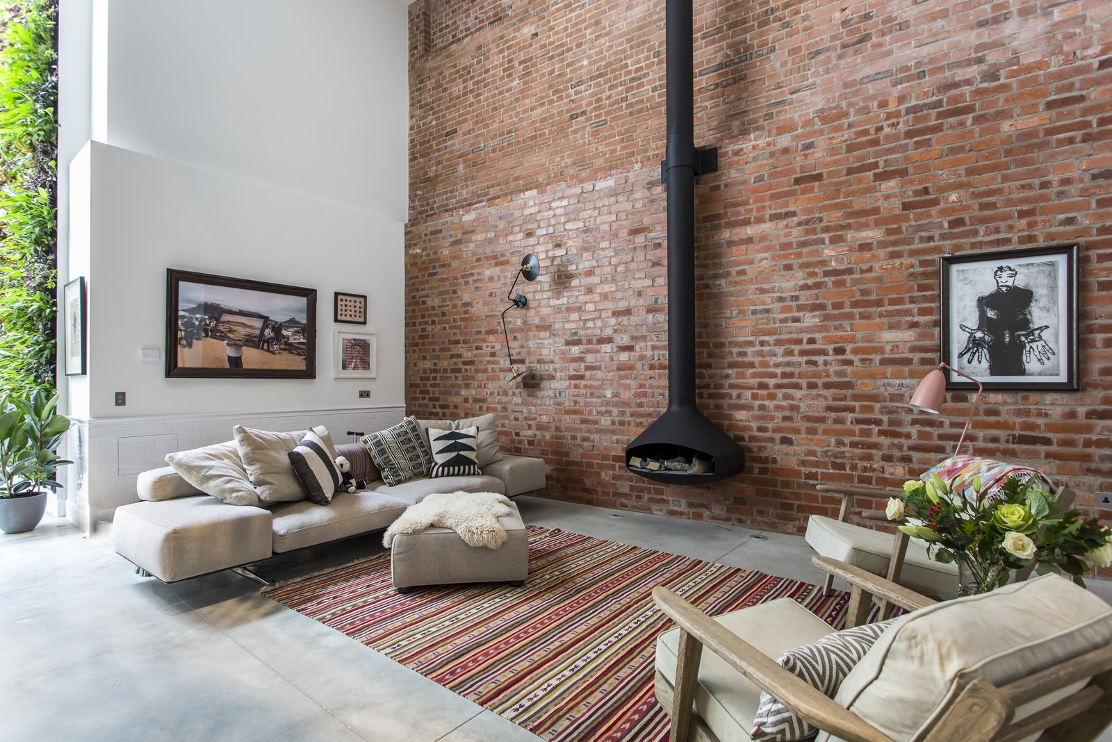 Living Room, Concrete Floor, Chair, Floor Lighting, Wall Lighting, Wood Burning Fireplace, Rug Floor, Ottomans, Sofa, and Hanging Fireplace  Photo 1 of 8 in Stay in a Converted Victorian Cooperage in London