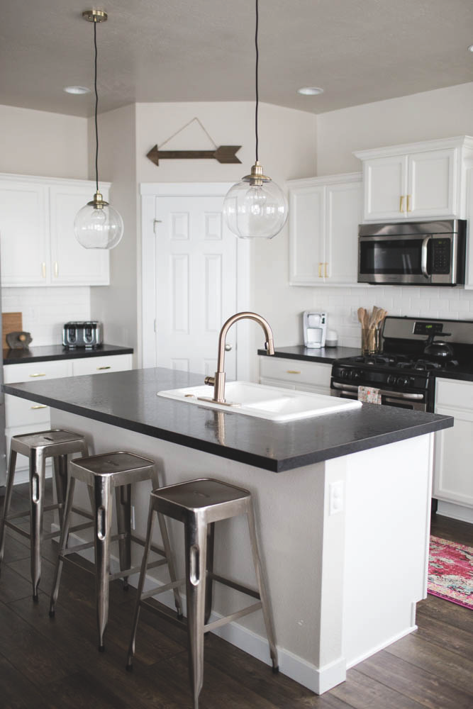 Kitchen with charcoal stone countertops white cabinets and exposed bulb pendant lighting.