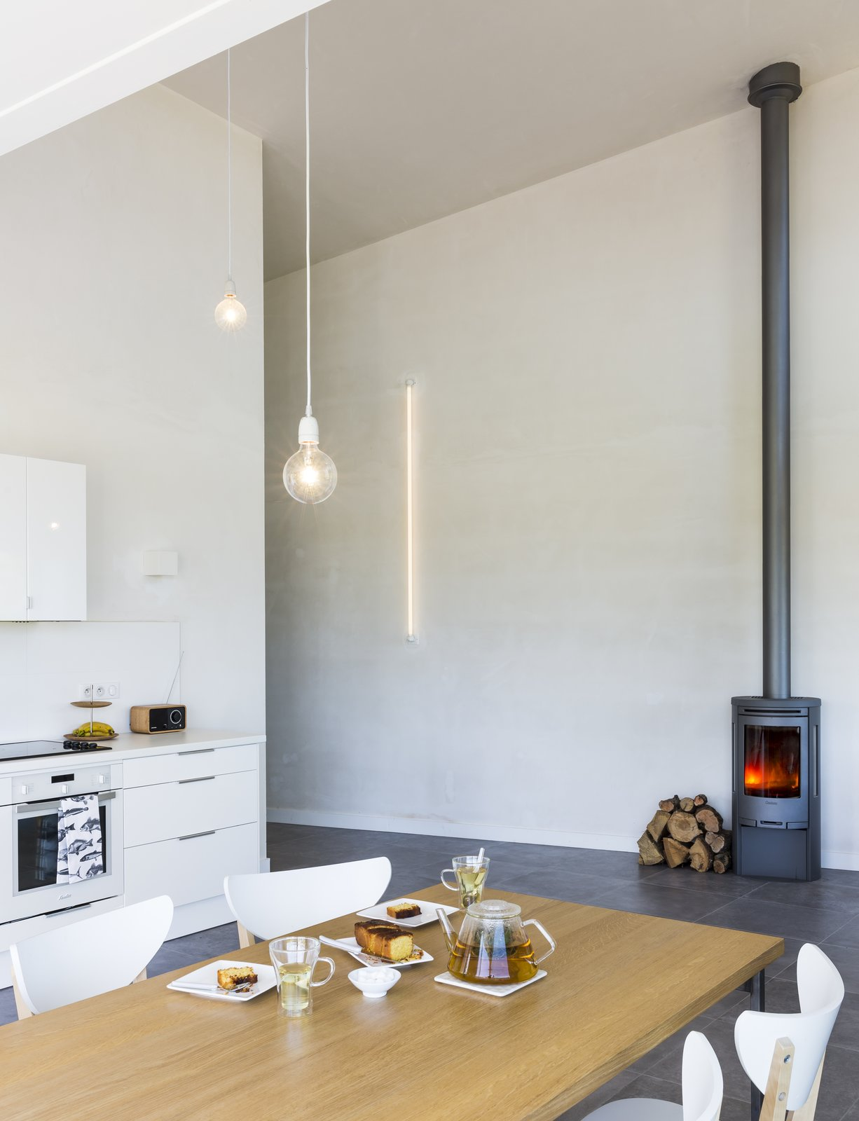A C500 wood-burning stove from Contura creates a cozy atmosphere.  Photo 5 of 10 in Framing the Landscape and Capturing Light, a Photographer's Home and Studio Echoes His Work