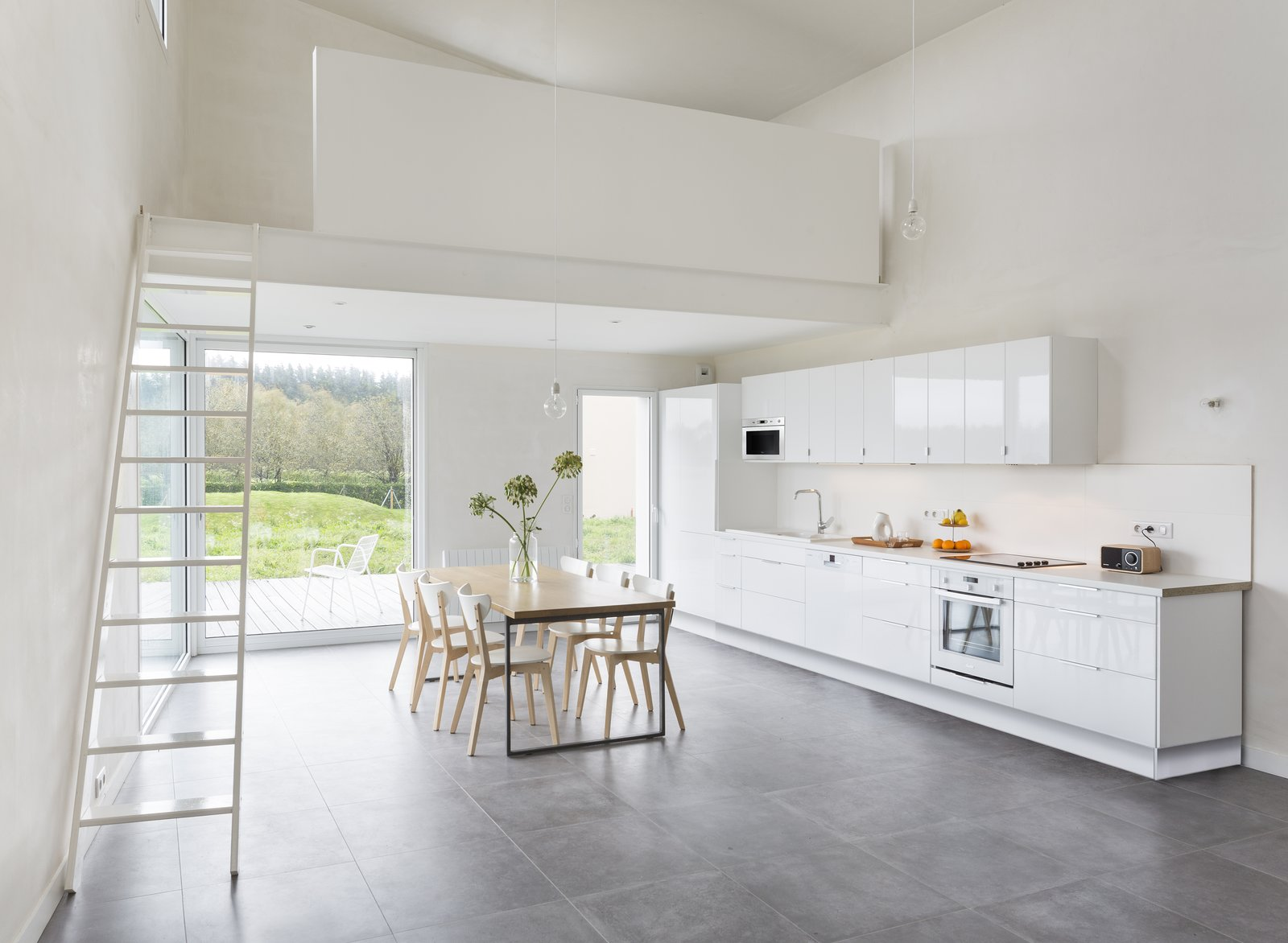 A sleek, minimal kitchen with lacquered MDF cabinets provides a glossy contrast to the unpainted walls.  Photo 6 of 10 in Framing the Landscape and Capturing Light, a Photographer's Home and Studio Echoes His Work
