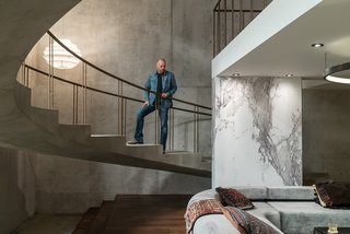 Above, Novotny surveys the set. The concrete walls and floors were created by pouring a quarter-inch layer of concrete over plywood. While marble is traditionally painted for film and television sets, Novotny took a different route to save time. After hunting down the perfect slab of Calacatta marble in a showroom, he hired a photographer to capture a high-resolution image that was then printed on sheets of white plastic by Astek Wallcovering in Los Angeles.
