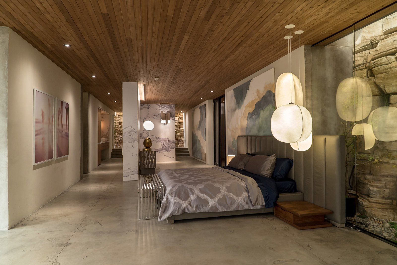 Kyle West's bedroom features an arrangement of Mori pendant lights by Rich Brilliant Willing and the Oviedo Leather Chair by Restoration Hardware, not pictured. A cloud mural painted by local artist Graeme Berglund contributes to an airy atmosphere.  Photo 7 of 10 in Here's How Hollywood Builds a Malibu Dream Home—on a Vancouver Soundstage