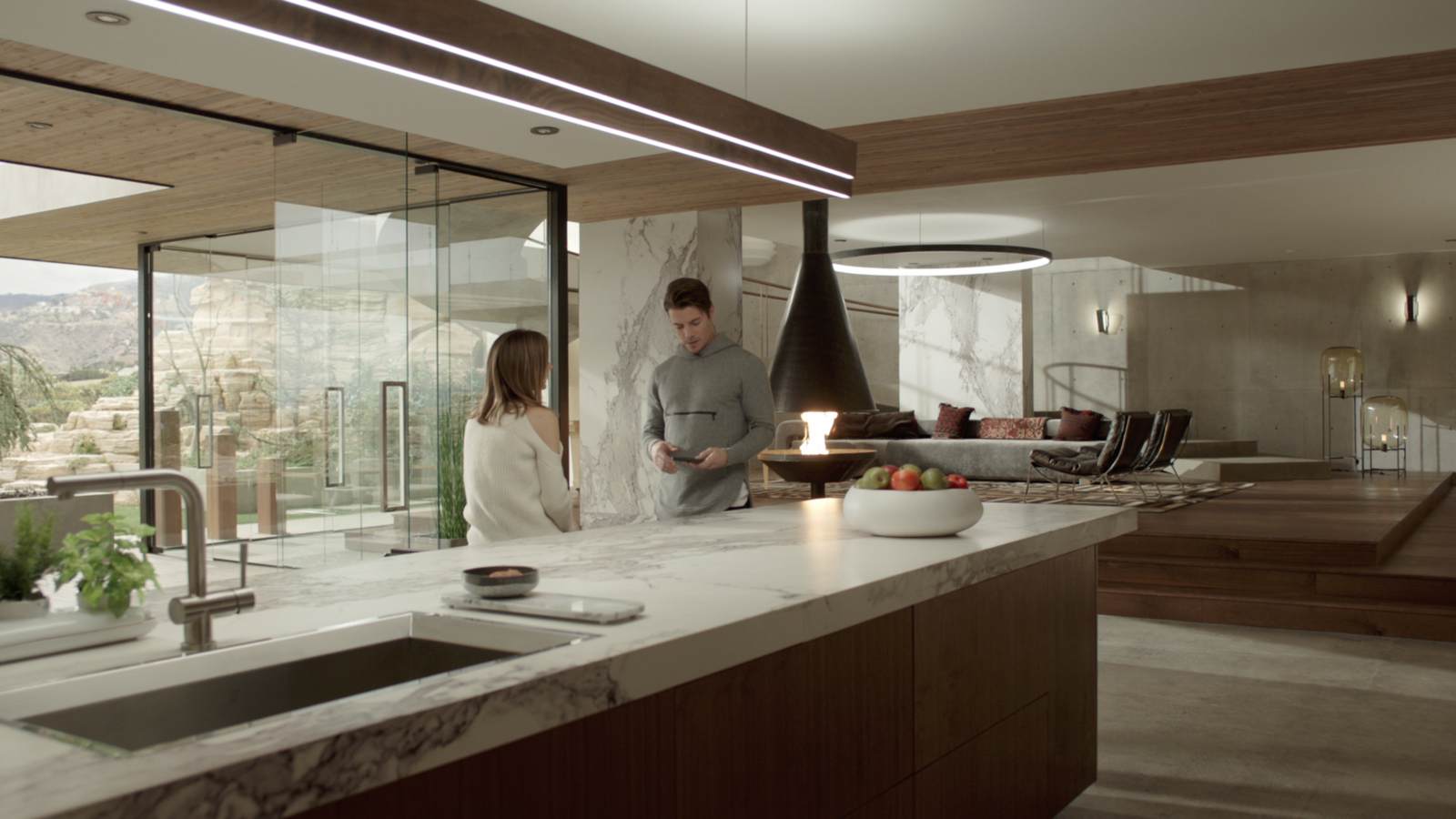 Kyle West and Megan Morrison, played by actress Christine Evangelista, have a conversation in the kitchen, which boasts walnut veneers. The glass panels that offer  Photo 8 of 10 in Here's How Hollywood Builds a Malibu Dream Home—on a Vancouver Soundstage