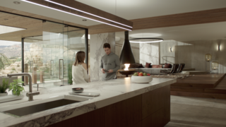 "Kyle West and Megan Morrison, played by actress Christine Evangelista, have a conversation in the kitchen, which boasts walnut veneers. The glass panels that offer ""oceanfront"" views are each three feet wide, and are held with a strip of metal that allows the panel to spin—which comes in handy to manipulate reflections during filming."