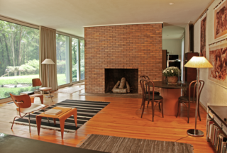 "Reminiscent of the Glass House, a monumental brick fireplace stands in the center of the living room. ""Because the home was designed for a couple without children, it's a very large, open space that was signature of the modern experiments at the time,"" says Matthew."