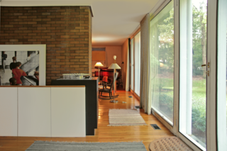 The entryway leads into the living room, and a low wall hides the staircase that leads to the lower level from view.