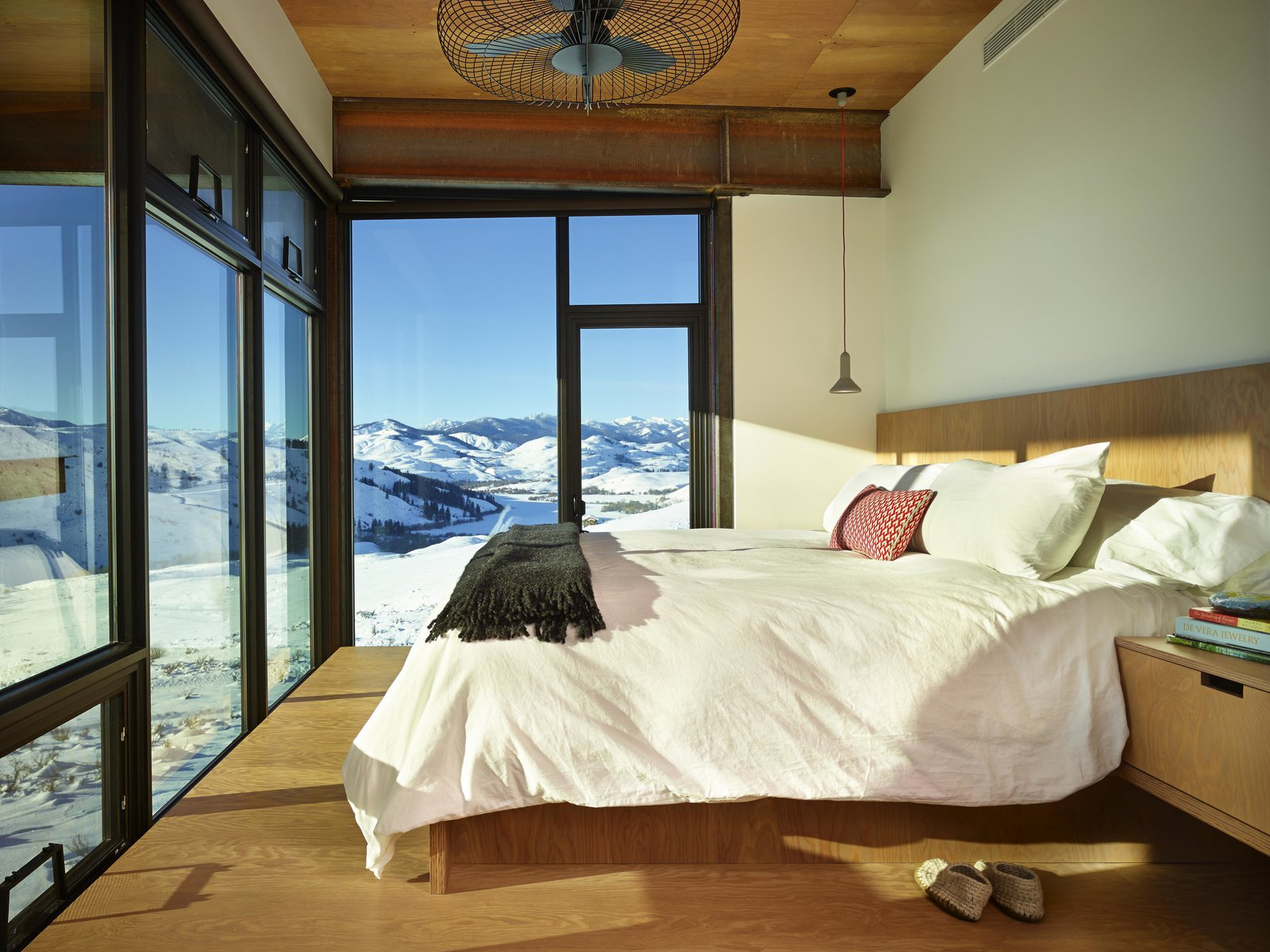 Bedroom, Medium Hardwood Floor, Pendant Lighting, and Bed The master bedroom, kids' bedrooms, and den are ensconced in the  Photo 9 of 11 in A Steel-and-Glass Compound Is One Family's Launchpad For Adventure