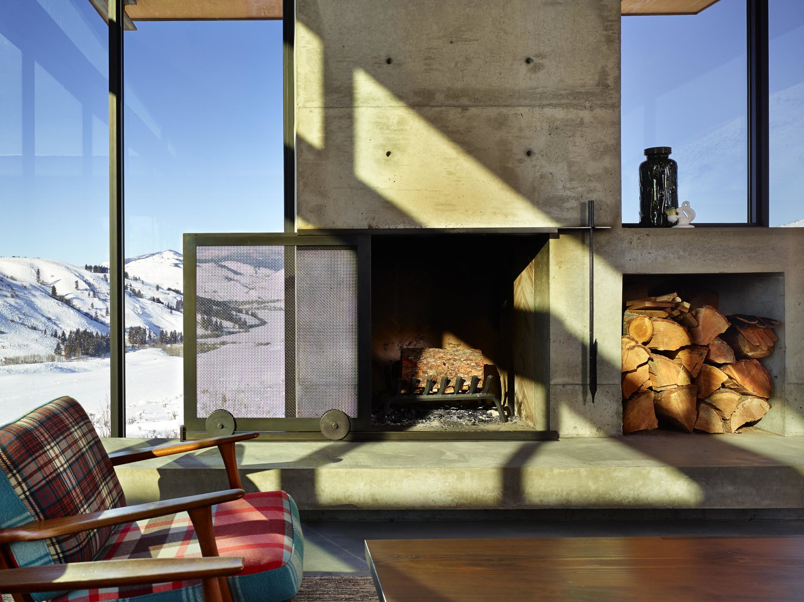 Living Room, Standard Layout Fireplace, and Chair A sliding mesh screen glides over the fireplace, which features a built-in cubby for a stockpile of wood.  Photo 4 of 11 in A Steel-and-Glass Compound Is One Family's Launchpad For Adventure
