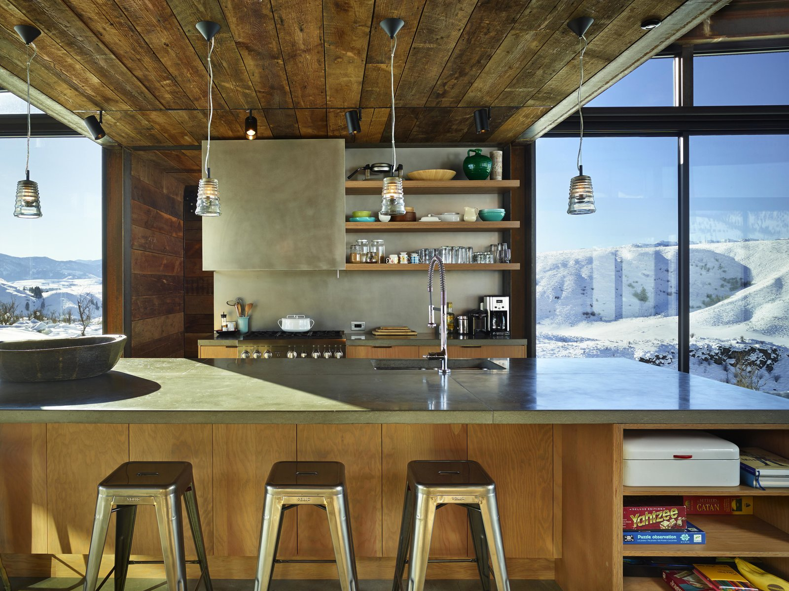 Kitchen, Concrete Counter, Wood Cabinet, and Pendant Lighting Wood siding salvaged from an old barn in Spokane, Washington, was repurposed for the project.  Photo 5 of 11 in A Steel-and-Glass Compound Is One Family's Launchpad For Adventure