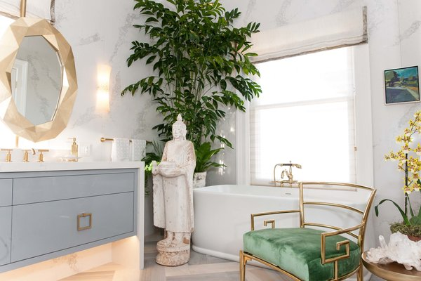 """In """"Master Bath: Restore and Refresh,"""" designer Cecilie Starin encourages contemplation with plants, Asian accents, natural objects, and art. The gold, faceted vanity mirrors slide apart to allow views of the bay."""