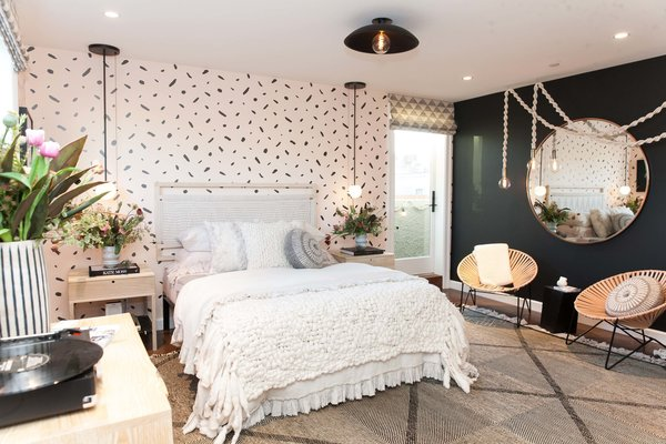 """Kristen Peña's goal for the teen bedroom was to create a """"cozy, livable haven for a 13-year-old girl that would embrace her during her transformation from girl to woman."""" The blush pink and black hues represent this dichotomy, while textural elements like a handwoven Peg Woodworking headboard and rope lights by local artist Windy Chien add warmth. """"We feel that texture is very important in creating both that cozy feel and a level of sophistication in the room,"""" says the designer."""