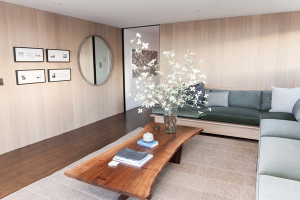 """The penthouse living room and bar by Catherine Kwong features a Nakashima Cocktail Table. Kwong flew to Pennsylvania to meet with George Nakashima's daughter, Mira, and selected the slab of walnut that would anchor the room. """"That was the first design decision made, and everything else followed,"""" says the designer."""
