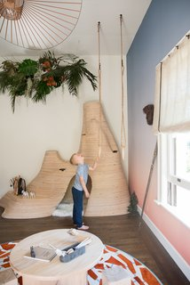 """The Great Exploration Kid's Bedroom"" by Sherry Hope-Kennedy is ""a space intended for climbing, hanging, and pure adventure—shelter for the seeker of all things fun and free,"" says the designer. Ombre wallpaper wraps around the room, providing an African backdrop to a tree fort-inspired bunk bed, carved gym rings, and a termite mound enclosure."