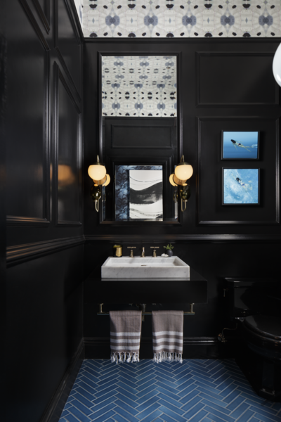 """Designed by Benni Amadi Interiors and Courtney Springer Interiors, the """"Moody Blues"""" powder room and vestibule pairs a marble sink with dramatic black walls that make the room seem more spacious, while blue tiles laid in a herringbone pattern reference the traditional architecture of the home."""