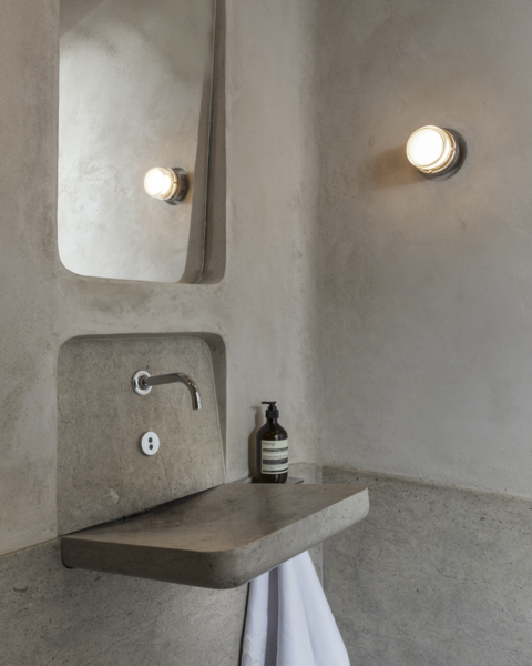 """Inspiration for the powder room by David Bjorngaard and Stephen Stout came from trips to Rome and Milan. """"The core concept of the bathroom is the Roman bath—the materiality of the limestone wainscot and the limestone plaster walls—and the simplicity of a Roman fountain [represented by] a simple faucet that empties into a sleek basin,"""" says Bjorngaard."""