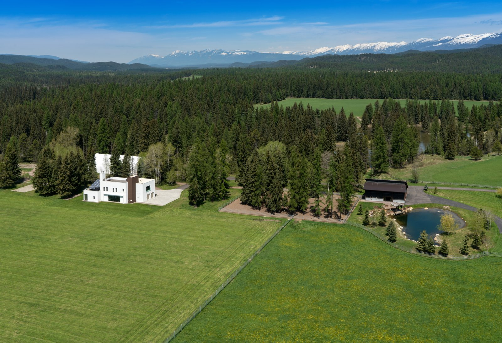 Outdoor, Trees, Woodland, Grass, and Back Yard With easy access to the Whitefish Mountain Resort and Glacier National Park, the home offers plenty to explore—on the grounds and off.  Photo 11 of 11 in A Rock & Roll Hall of Famer's Picturesque Montana Retreat Is Going Up For Auction