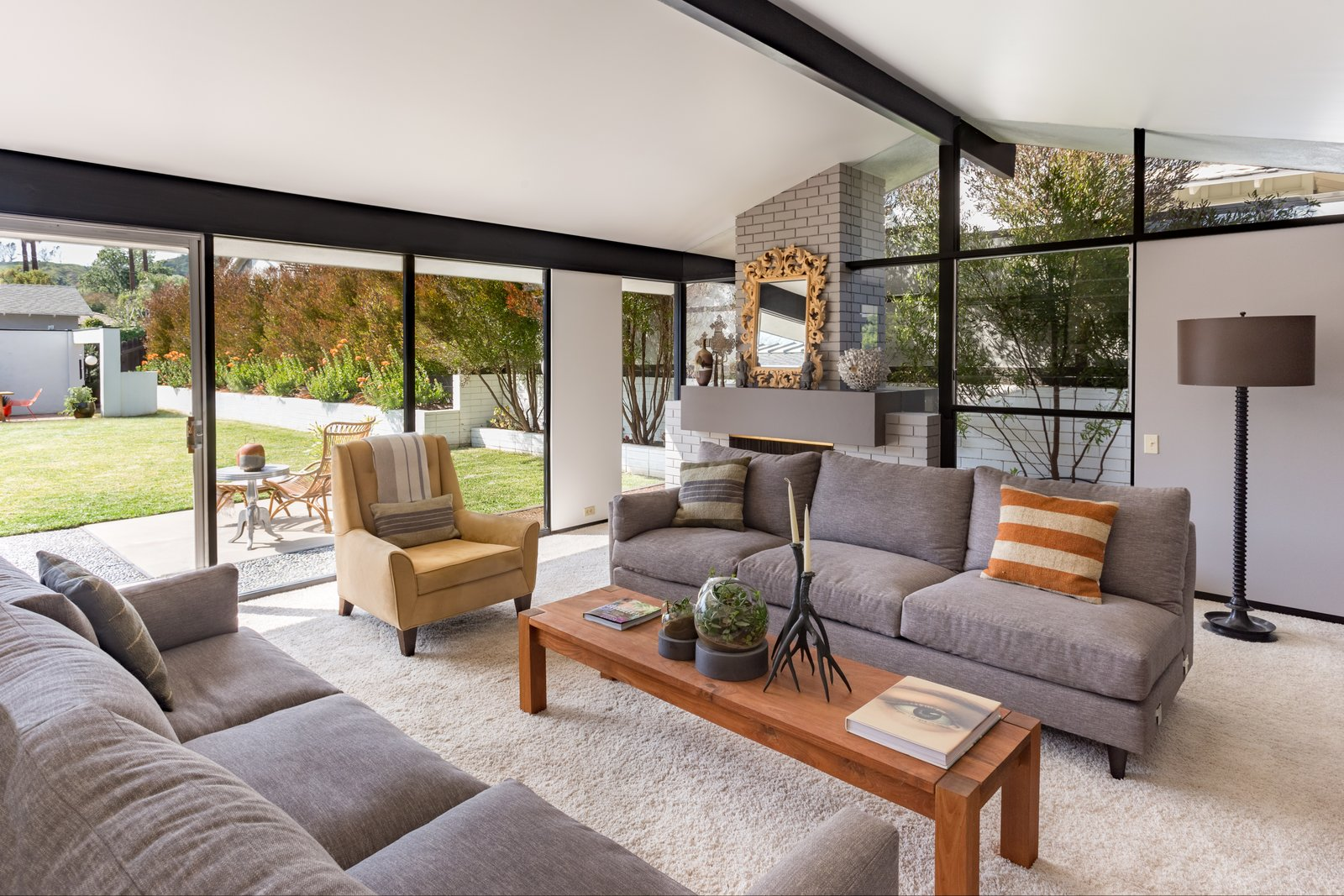 Living Room, Sofa, Chair, Coffee Tables, Floor Lighting, and Standard Layout Fireplace  Photo 5 of 14 in Offered at $899K, a Restored Midcentury Abode Shines in Southern California