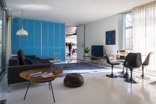 A Bertoia Bench in white oak supports the TV in the family room, while a 50th anniversary-edition Saarinen Tulip Table and Chairs provide a dark contrast to the cheery interiors. The vintage spun aluminum light fixture is also original to the house. Notice how the Knoll curtain, when open, can be neatly tucked into a nook beside the blue closets.