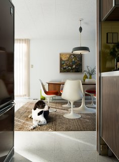 A Rare Midcentury Prefab Looks Just Like it Did in 1958—Down to the Knoll and Paul McCobb Interiors - Photo 7 of 13 - The homeowners love to host guests in the dining room, which features another set of Saarinen furniture. Banksy, a rescue lab and setter mix, takes a break from chasing toys up and down the hallways.