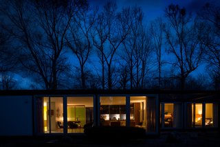 Generous stretches of glass allow the house to glow at night.