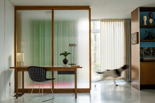 """A Paul McCobb reeded glass panel provides a contemplative backdrop for a walnut Knoll writing desk and Bertoia Side Chair. """"They feel like the soul of the house,"""" says Coscarelli of the partitions. """"They change constantly with the light."""" A Noguchi Number 9 Lamp is one of several original to the house."""