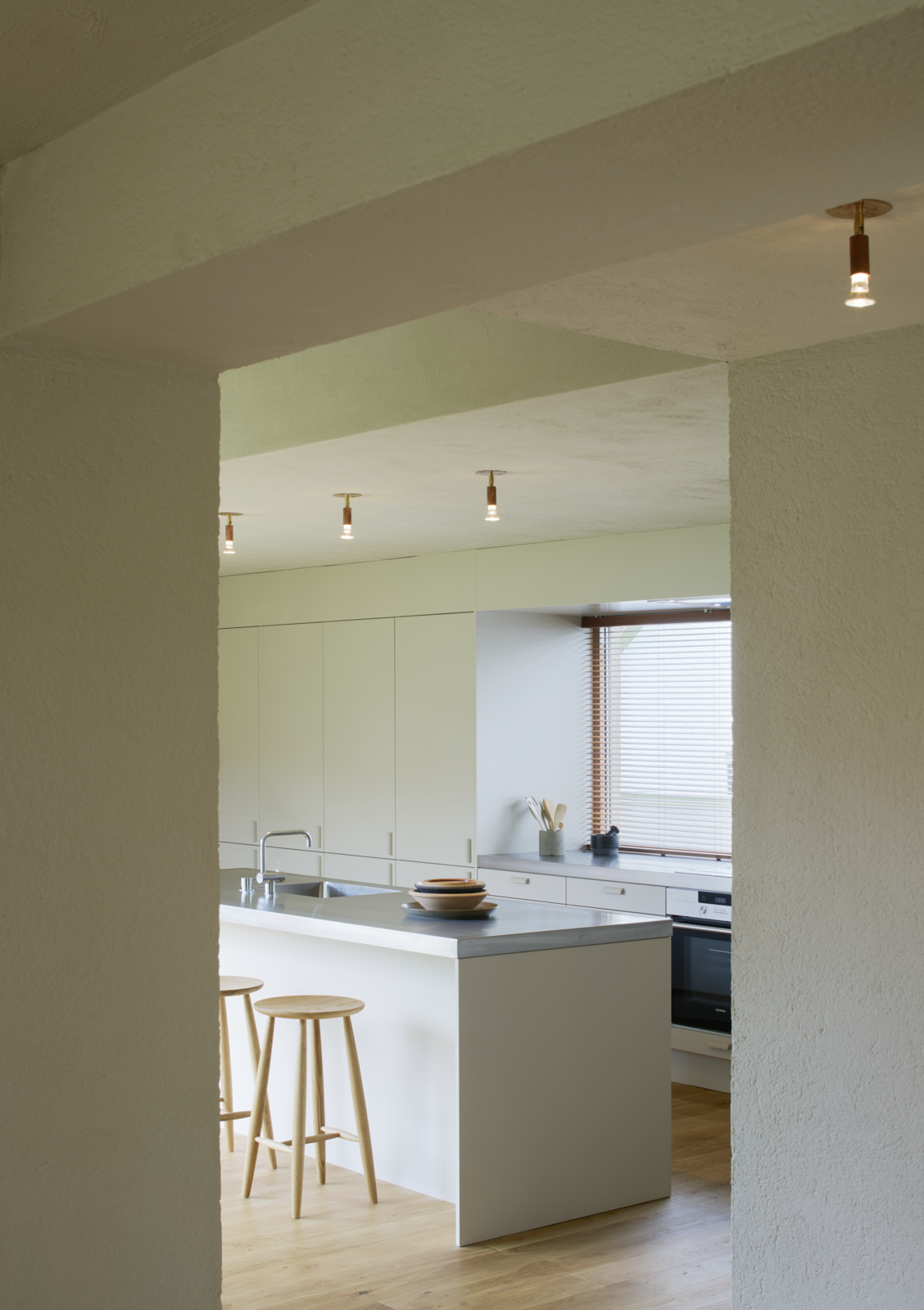 Kitchen, Medium Hardwood Floor, White Cabinet, Metal Counter, and Ceiling Lighting  Photo 6 of 12 in Sleek Scandinavian Design Permeates a Family's Summer House in an Old Fishing Village
