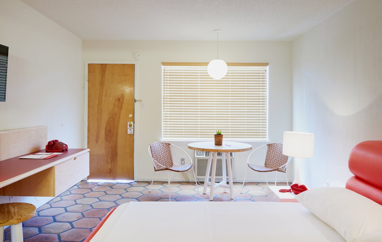 Bedroom, Night Stands, Pendant Lighting, Terra-cotta Tile Floor, Bed, Table Lighting, and Chair  Photo 6 of 13 in The Rejuvenated Austin Motel Welcomes Guests With Upbeat, Midcentury-Modern Vibes