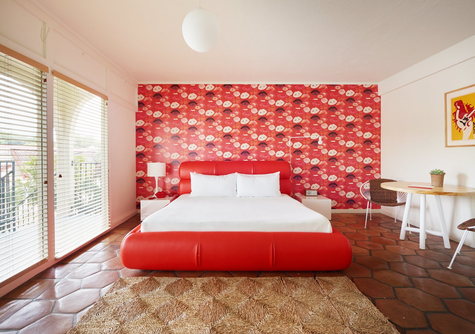Bedroom, Table Lighting, Pendant Lighting, Night Stands, Bed, Rug Floor, Chair, Wall Lighting, and Terra-cotta Tile Floor  Photo 1 of 13 in The Rejuvenated Austin Motel Welcomes Guests With Upbeat, Midcentury-Modern Vibes