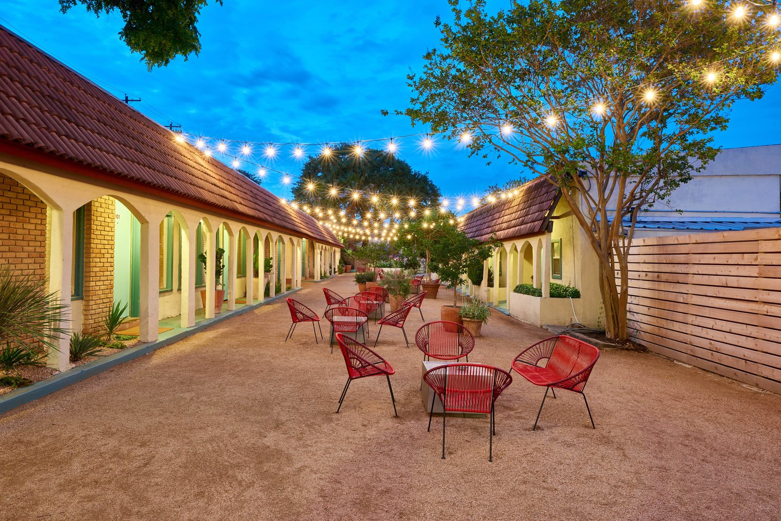 Outdoor, Side Yard, Horizontal Fences, Wall, Large Patio, Porch, Deck, Trees, Wood Fences, Wall, Hanging Lighting, and Raised Planters  Photo 7 of 13 in The Rejuvenated Austin Motel Welcomes Guests With Upbeat, Midcentury-Modern Vibes