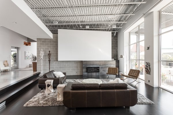Living Room, Dark Hardwood Floor, Chair, Sofa, End Tables, and Gas Burning Fireplace  Photo 8 of 12 in A Converted Ink Factory in Downtown Indianapolis Asks $2.6M