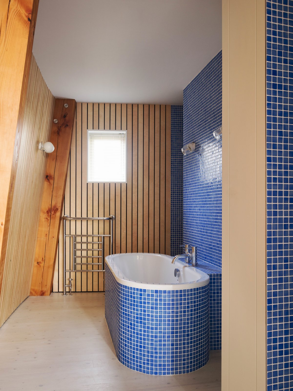Bath Room, Light Hardwood Floor, Soaking Tub, Wall Lighting, Freestanding Tub, and Ceramic Tile Wall  Photos from Resembling the Inverted Hull of a Ship, an English Guest House Pays Homage to the Harbor