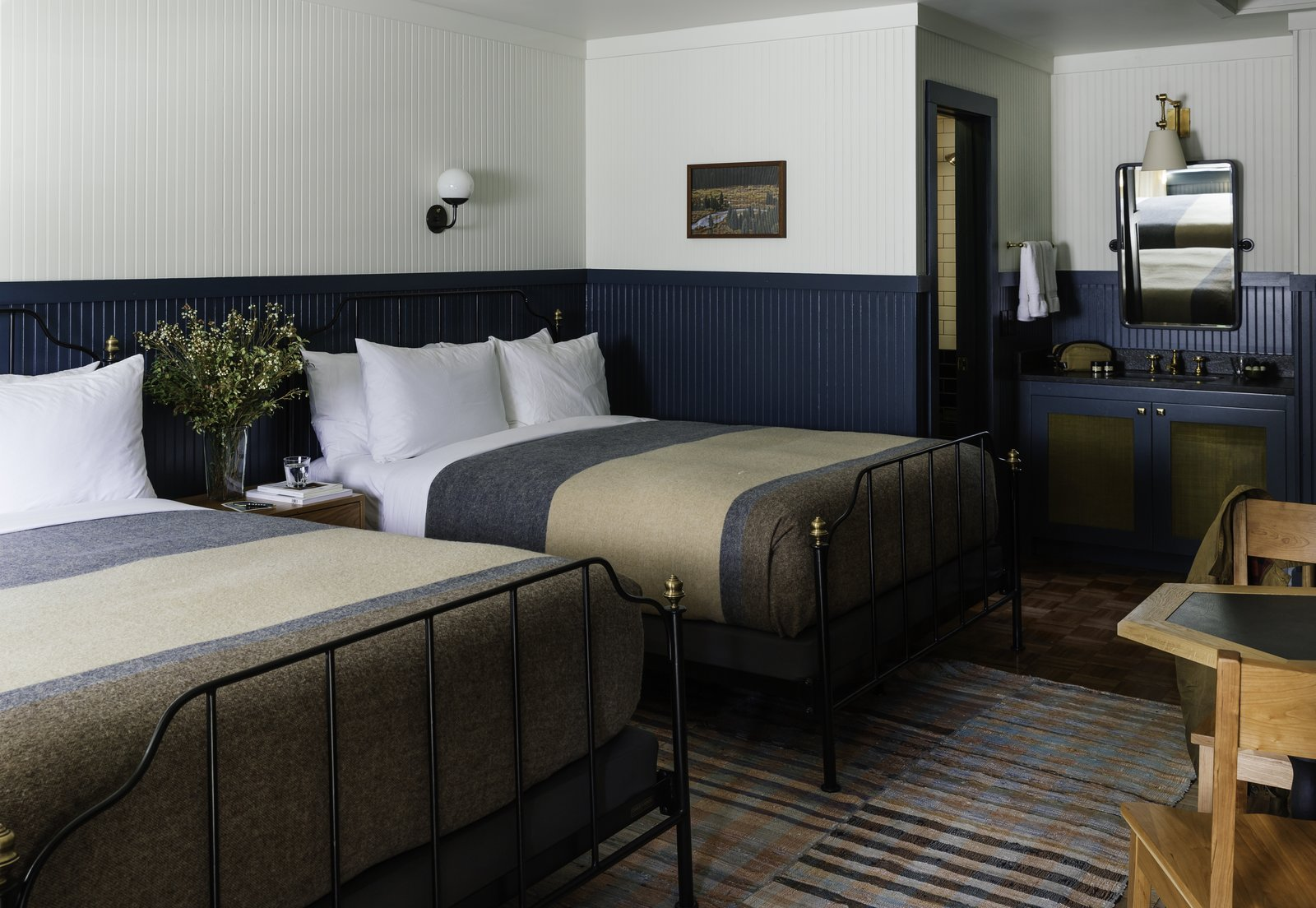 Bedroom, Rug Floor, Night Stands, Wall Lighting, Bed, Medium Hardwood Floor, and Chair  Photo 4 of 12 in Classic West Meets Contemporary Cool at the Anvil Hotel in Jackson, Wyoming