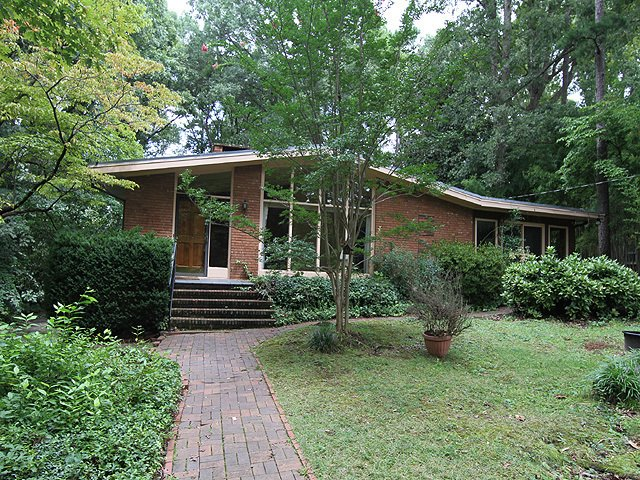 Before the renovation, 3322 Ocotea Street had a poorly built sunroom on the right side.  Photo 2 of 14 in Elegantly Renovated, a Midcentury Home in Raleigh Asks $975K