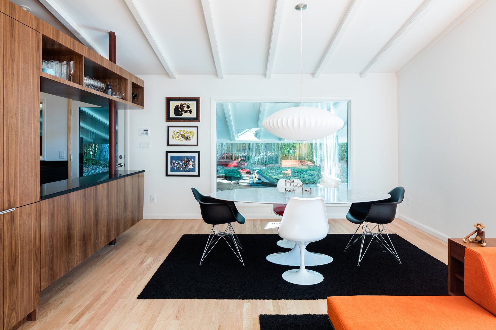Dining Room, Pendant Lighting, Light Hardwood Floor, Chair, Table, Storage, and Shelves  Photo 8 of 14 in Elegantly Renovated, a Midcentury Home in Raleigh Asks $975K