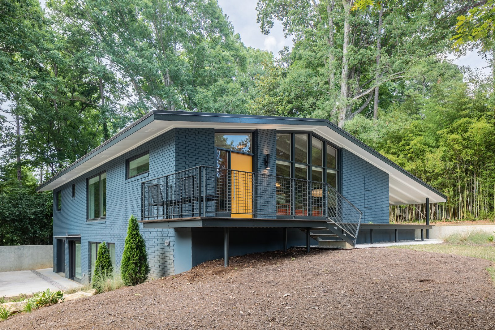 Outdoor, Trees, Wood Patio, Porch, Deck, Front Yard, Small Patio, Porch, Deck, and Metal Fences, Wall  Photo 3 of 14 in Elegantly Renovated, a Midcentury Home in Raleigh Asks $975K
