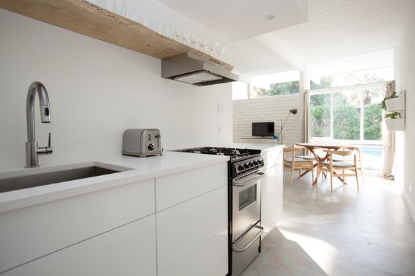 The Amado kitchen with white cabinets and raw wood shelf above kitchen range and hood.