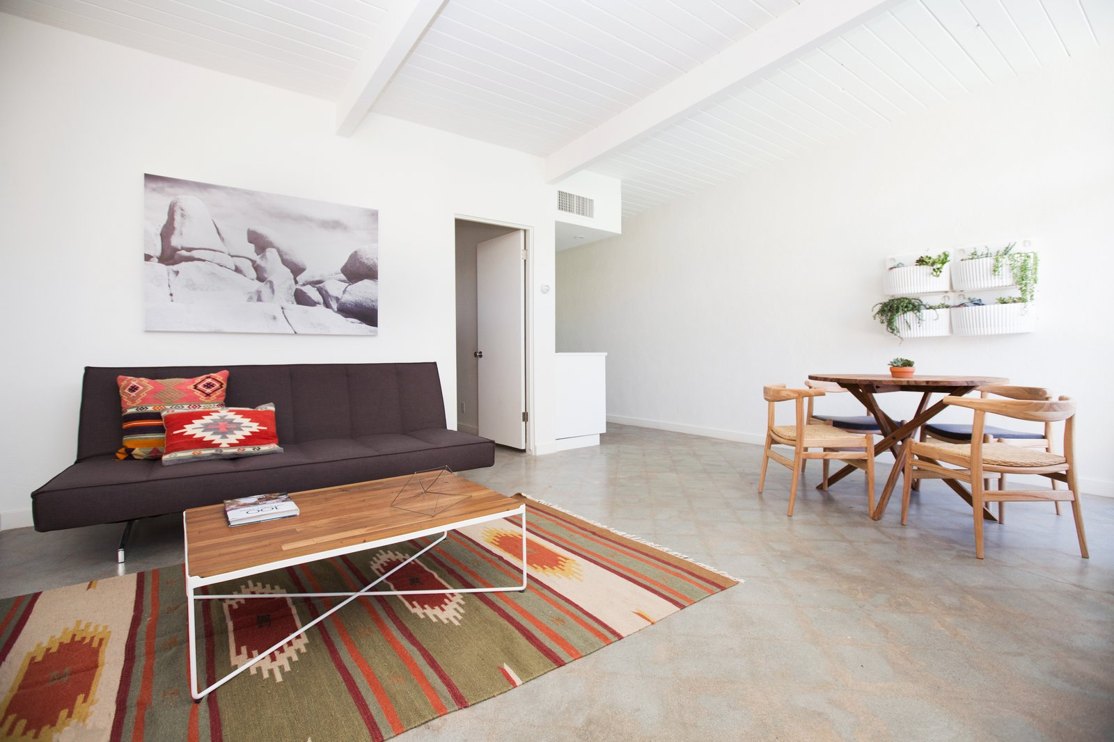 The Amado living area with concrete floors and walnut wood stained furnishings.
