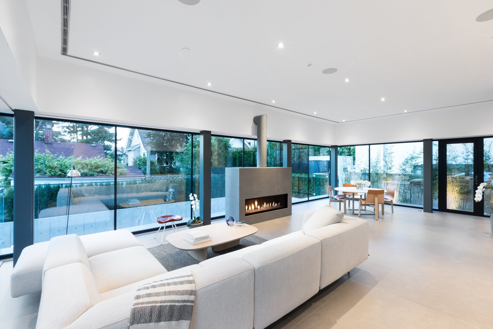 Living Room, Ribbon Fireplace, Gas Burning Fireplace, Rug Floor, Sectional, Coffee Tables, Chair, Recessed Lighting, Floor Lighting, Table, and Stools  Photo 4 of 12 in Wrapped in Galvanized Steel, 'Cube House' in Vancouver Asks $12.8M