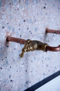 Copper piping for faucets extends out from a terrazzo-covered bathroom.